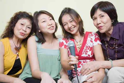 Portrait of two young women singing with their grandmothers into microphones : Stock Photo