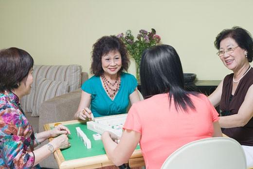 Three senior women and a mature woman playing mahjong : Stock Photo