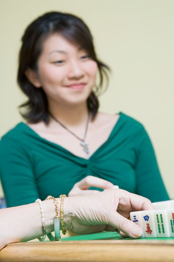 Close-up of a woman's hand playing with blocks and a young woman sitting in the background : Stock Photo