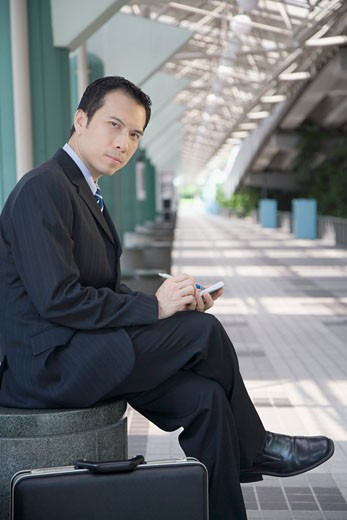 Portrait of a businessman sitting and using a palmtop : Stock Photo