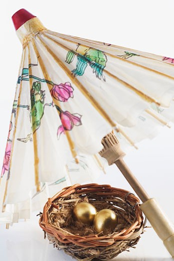 Stock Photo: 1768R-11143 Close-up of golden eggs in a bird's nest with a parasol