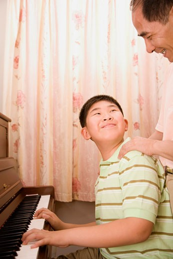 Mature man teaching his grandson how to play a piano and smiling : Stock Photo