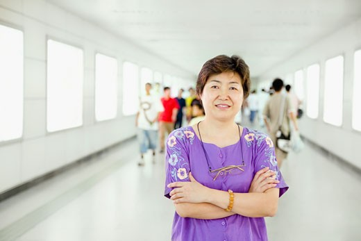 Portrait of a mature woman standing with her arms crossed in a corridor : Stock Photo