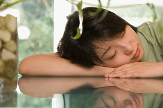 Female office worker napping at a table : Stock Photo