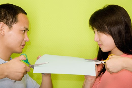 Stock Photo: 1768R-12519 Close-up of a young man and a young woman cutting a paper with scissors
