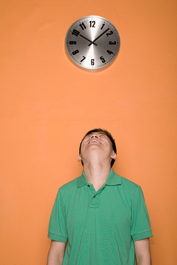 Stock Photo: 1768R-12940 Male office worker looking at a clock and smiling
