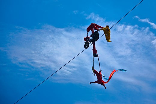 Low angle view of three people performing stunt on a rope, Emerald Valley, Huangshan, Anhui Province, China : Stock Photo