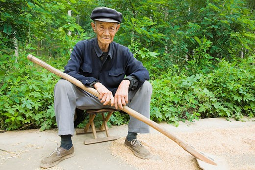 Stock Photo: 1768R-13516 Portrait of a farmer sitting on a stool in a field, Zhigou, Shandong Province, China