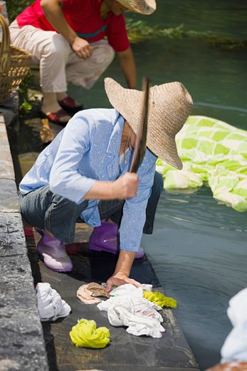 Woman washing clothes at riverside, Xidi, Anhui Province, China : Stock Photo