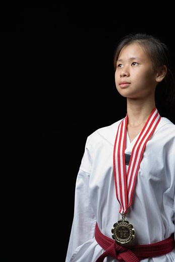 Young woman standing with a medal around her neck : Stock Photo