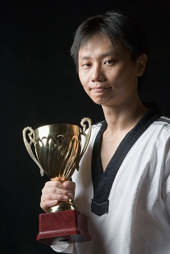 Portrait of a young man holding a trophy : Stock Photo