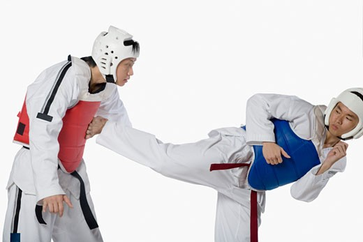 Close-up of a mid adult man practicing kickboxing with a young man : Stock Photo