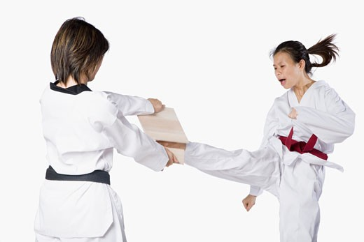 Close-up of two young women practicing kickboxing : Stock Photo