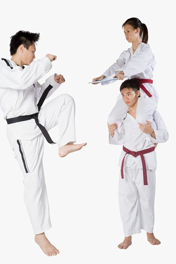 Mid adult man practicing kickboxing with a young man and a young woman : Stock Photo