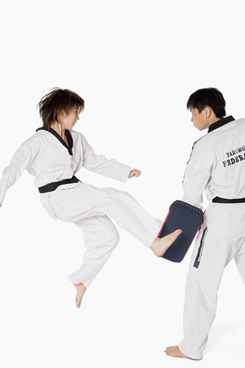 Female karate instructor teaching martial arts to a young man : Stock Photo