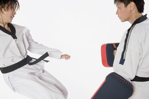 Stock Photo: 1768R-14623 Female karate instructor teaching martial arts to a young man