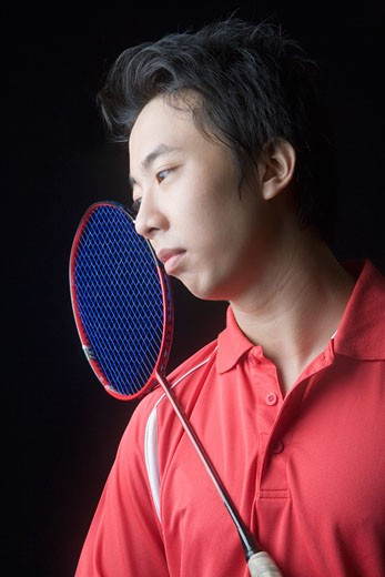 Close-up of a young man with a badminton racket : Stock Photo