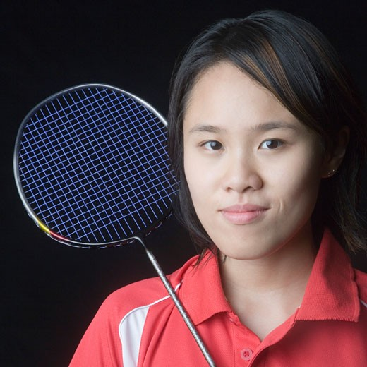 Portrait of a young woman with a badminton racket : Stock Photo