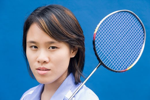 Stock Photo: 1768R-14724 Portrait of a young woman with a badminton racket