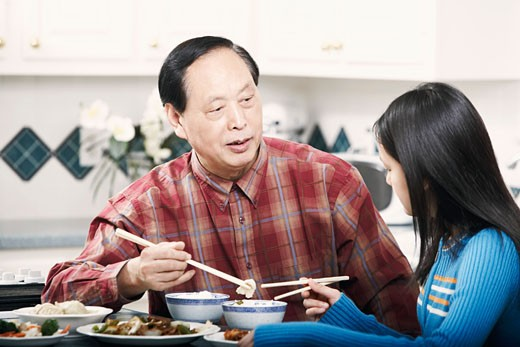 Grandfather and his granddaughter sitting at a table : Stock Photo