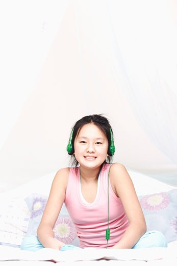 Portrait of a girl wearing headphones listening to music : Stock Photo