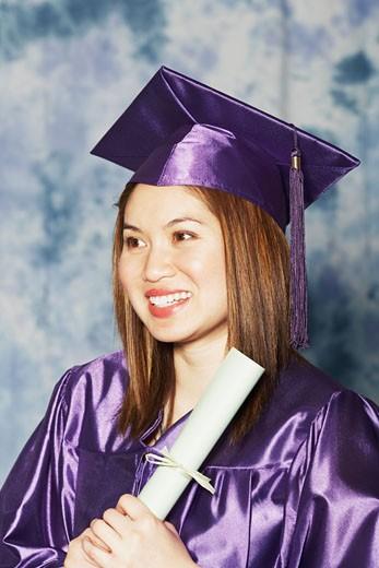 Close-up of a female graduate holding a diploma : Stock Photo
