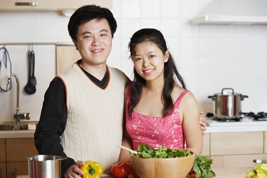 Portrait of a young man standing with a mid adult woman in the kitchen : Stock Photo