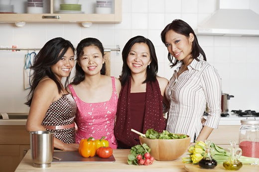 Portrait of a mid adult woman standing with three young women in the kitchen : Stock Photo