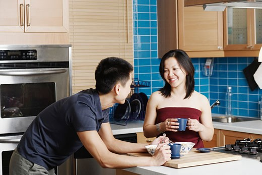 Close-up of a young couple holding cups in the kitchen : Stock Photo