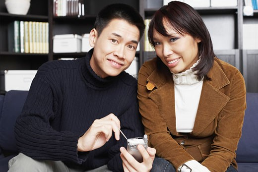 Portrait of a young man sitting with a young woman on a couch holding a mobile phone : Stock Photo