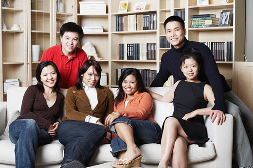 Portrait of four young women and two young men sitting on a couch : Stock Photo