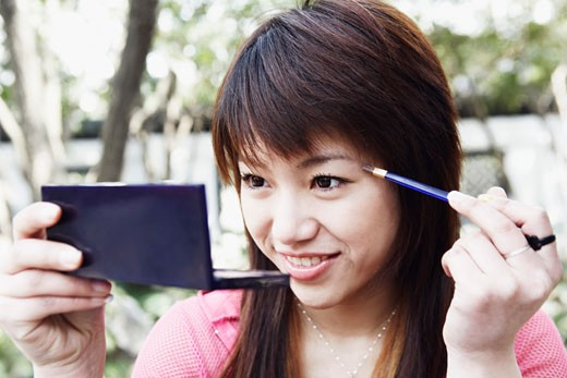 Close-up of a young woman applying make up : Stock Photo