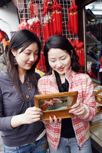 Two young women looking at a jewelry box smiling : Stock Photo