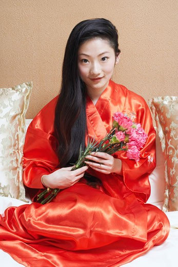 Stock Photo: 1768R-3867 Portrait of a young woman holding a bunch of flowers