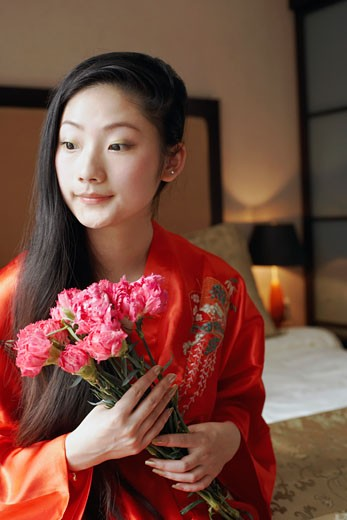 Close-up of a young woman holding a bunch of flowers : Stock Photo