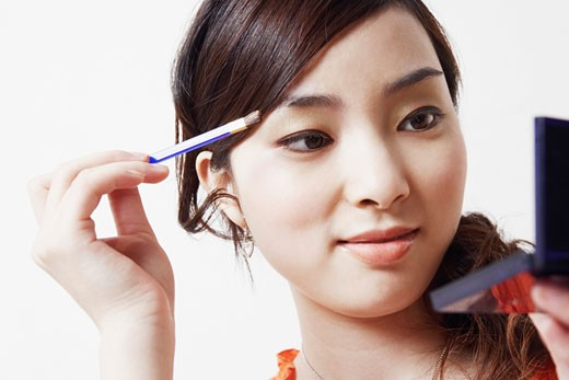Close-up of a young woman holding a make-up brush and a hand mirror : Stock Photo