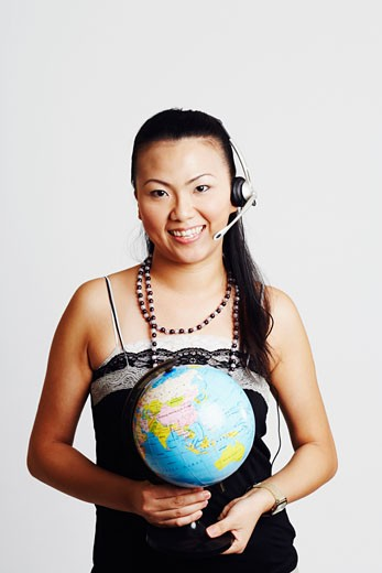 Stock Photo: 1768R-5415 Portrait of a young woman wearing a headset and holding a globe