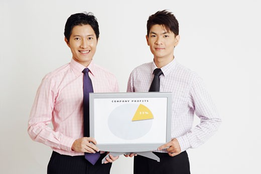 Portrait of two businessmen holding a progress report and smiling : Stock Photo