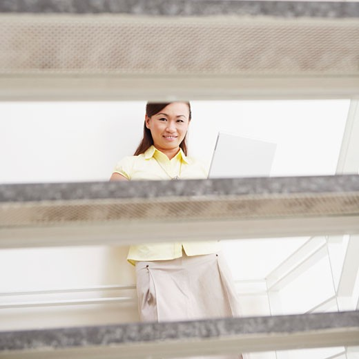 Stock Photo: 1768R-5661 Portrait of a young woman leaning against a wall and using a laptop