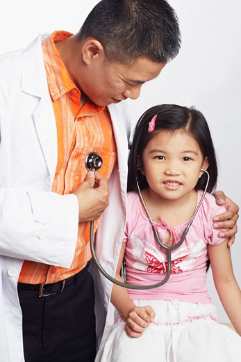 Close-up of a girl listening to a male doctors heart beat with a stethoscope : Stock Photo
