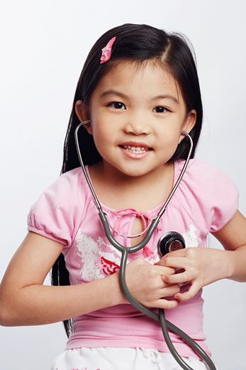 Portrait of a girl listening to her heart beat with a stethoscope : Stock Photo