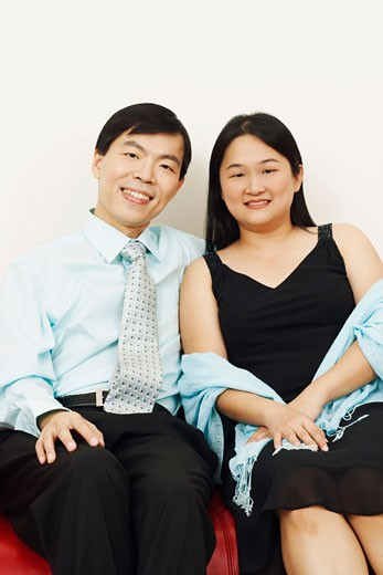 Portrait of a businessman and a mid adult woman sitting together on a couch and smiling : Stock Photo