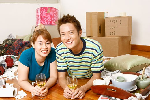 Stock Photo: 1768R-6765 Portrait of a young couple lying on the floor and holding glasses of wine