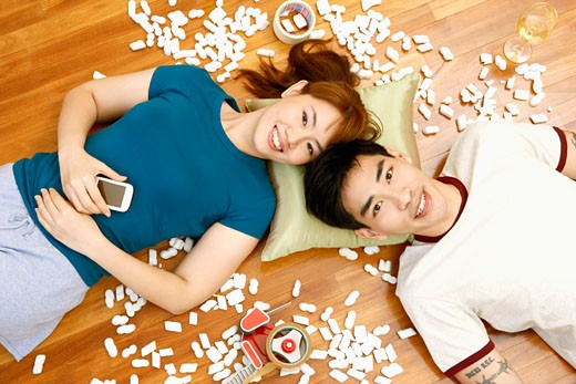 High angle view of a young couple lying on the floor and smiling : Stock Photo