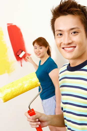 Stock Photo: 1768R-6856 Portrait of a young man holding a paint roller with a young woman standing in the background