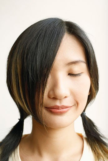 Close-up of a young woman with her eyes closed : Stock Photo