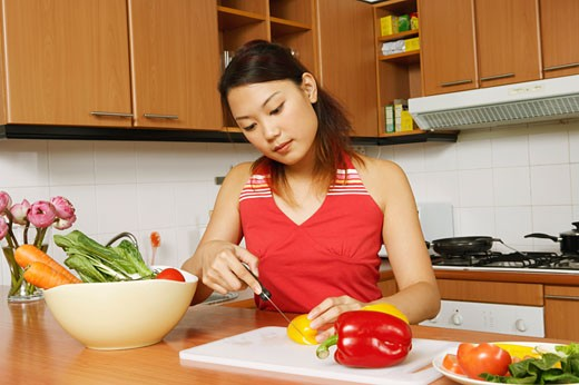 Young woman cutting vegetables at a kitchen counter : Stock Photo