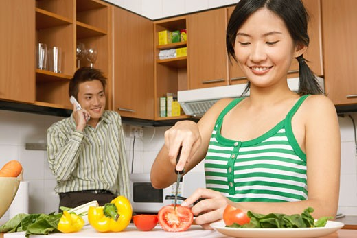 Stock Photo: 1768R-6963 Close-up of a young woman cutting vegetables in the kitchen with a young man talking on a mobile phone
