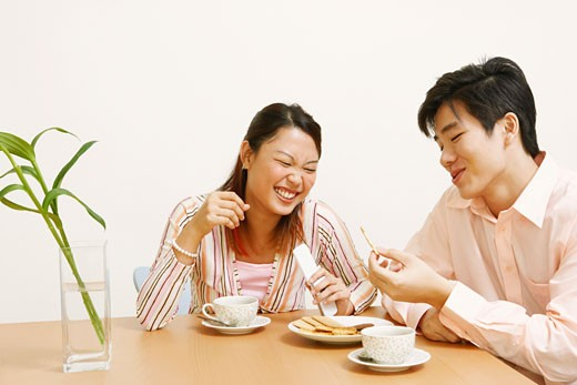 Close-up of a young couple looking at a cookie and smiling : Stock Photo