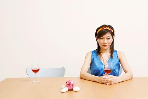 Portrait of a young woman holding a glass of wine : Stock Photo